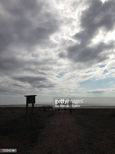 Silhouette Of Man On Beach Against Cloudy Sky