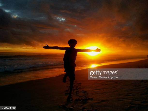 Silhouette Of Man On Beach At Sunset