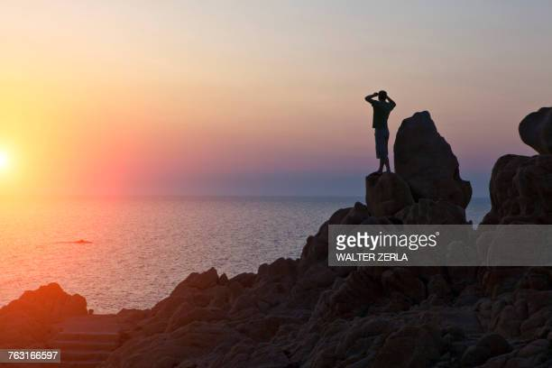 Silhouette of man on rocks looking away at sunset over sea, Olbia, Sardinia, Italy