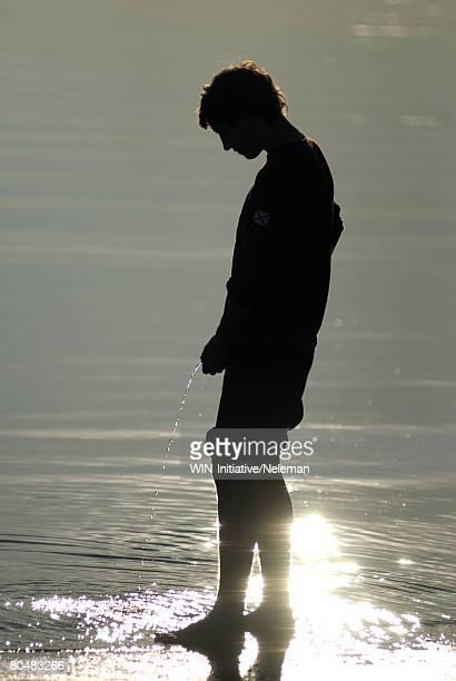 Silhouette of man peeing in the ocean