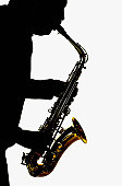 Silhouette of man playing a saxophone