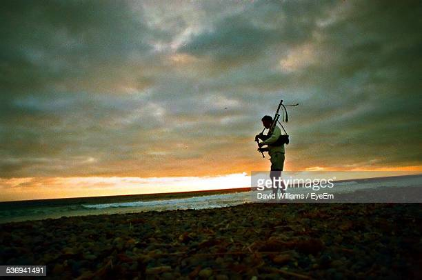 Silhouette Of Man Playing Bagpipe On Beach At Sunset