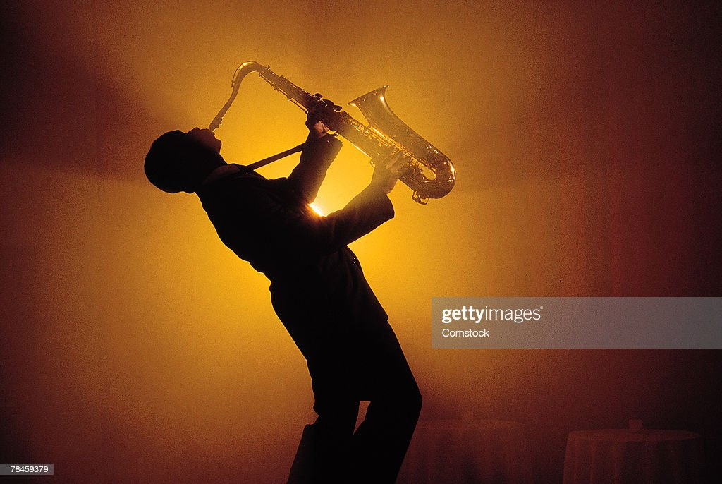 Silhouette of man playing saxophone : Stock Photo