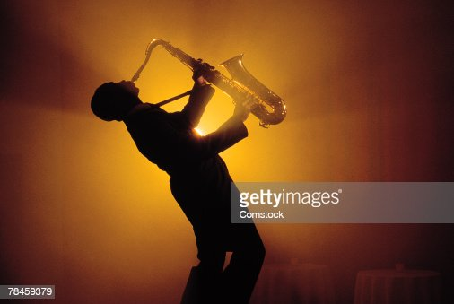 Silhouette of man playing saxophone
