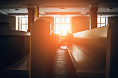 Silhouette of man praying in church in sunset light, toned