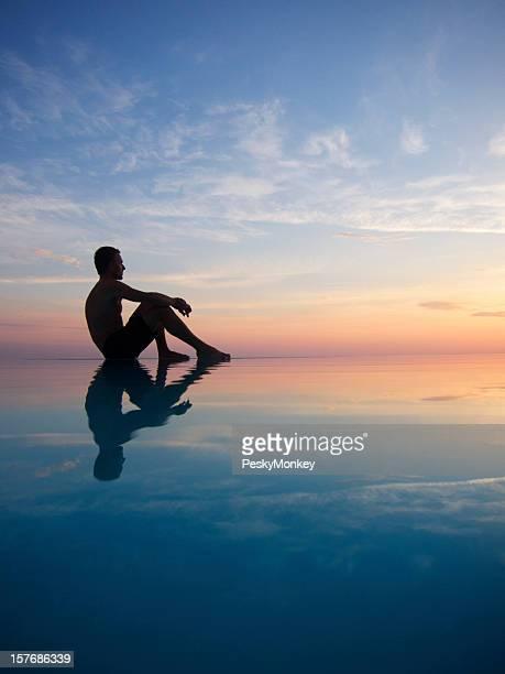 Silueta del hombre que reflejan en la piscina de borde infinito al atardecer