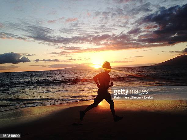 Silhouette Of Man Running On Beach