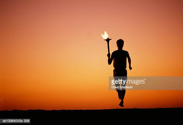 Silhouette of man running with torch at sunset