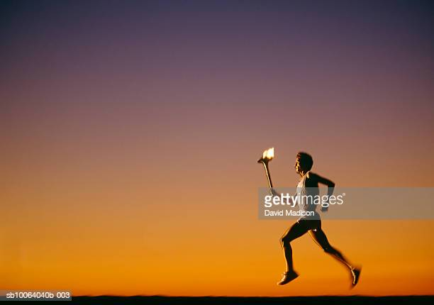 Silhouette of man running with torch at sunset, side view