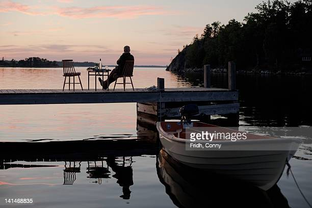 Silhouette of man sitting on pier