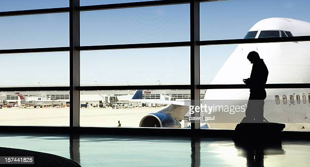 Silhouette of man talking on cell phone at airport.