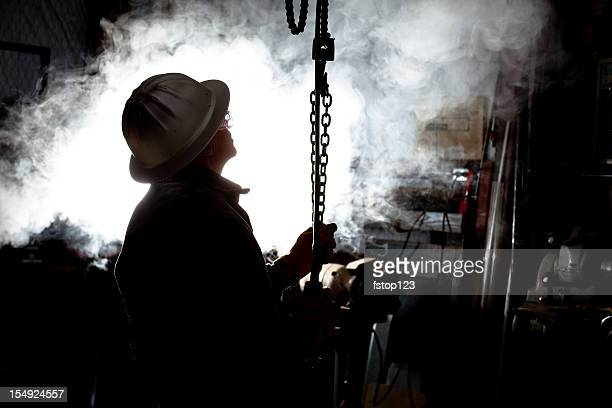 Silhouette of man using chain hoist in workshop.