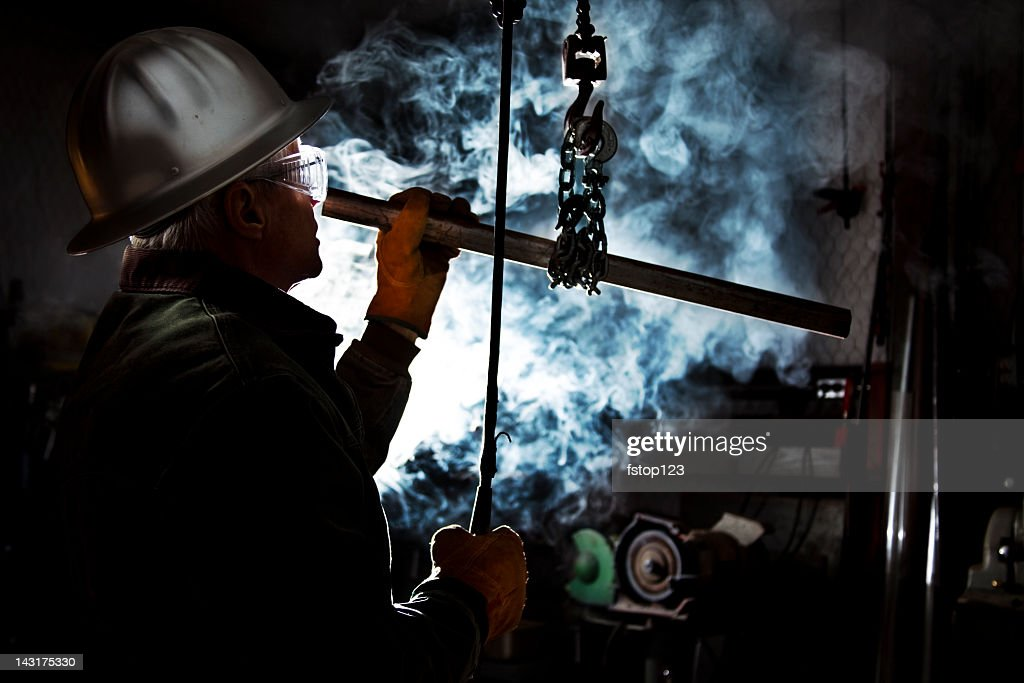 Silhouette of man using chain hoist in workshop.  Steam background : Stock Photo