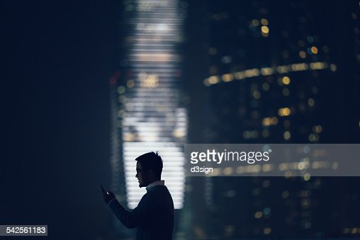 Silhouette of man using smartphone in city : Stock Photo