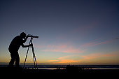 Silhouette of man using telescope at dusk, side view