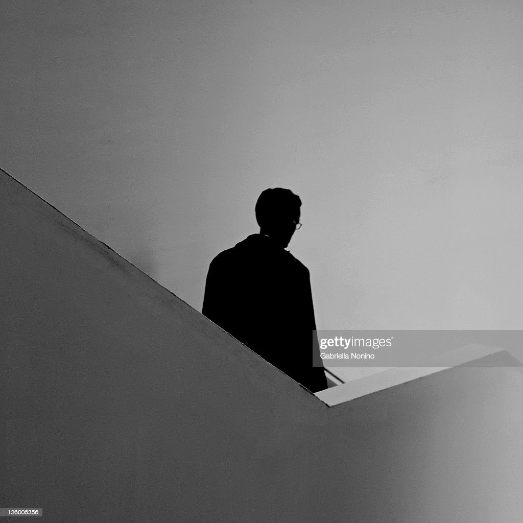 Silhouette Of Man Walking Down Stairs Stock Photo | Getty ...