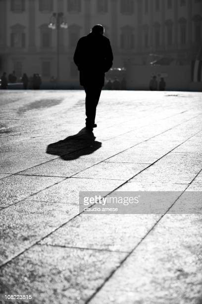 Silhouette of Man Walking Through Town Square. Black and White