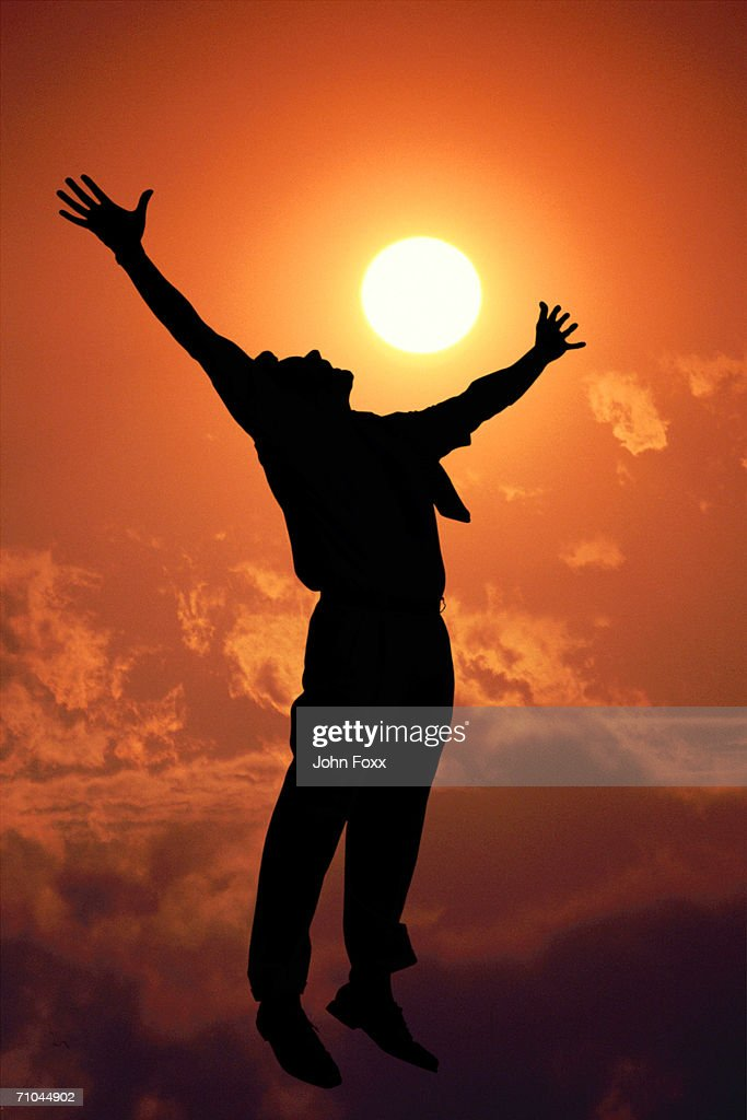 Silhouette of man with arms outstretched : Stock Photo
