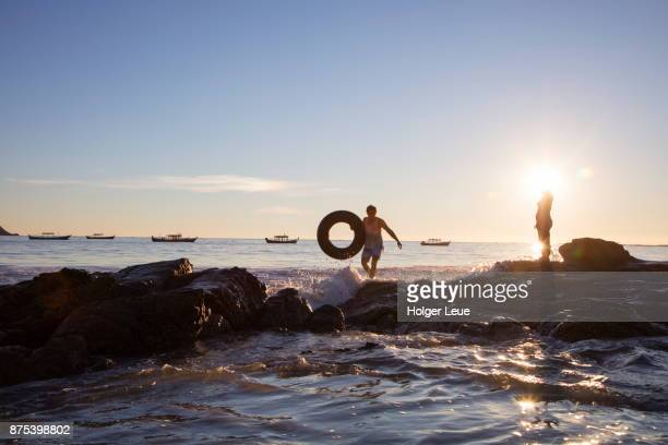 Silhouette of man with inner tube and woman standing on rock at Ngapali Beach at sunset, Ngapali, Thandwe, Myanmar