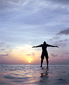 Silhouette of man with out-stretched arms, standing in ocean