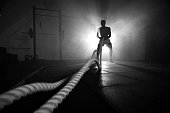 Silhouette of man working out with battle ropes at gym. Functional training. Sports and fitness concept.