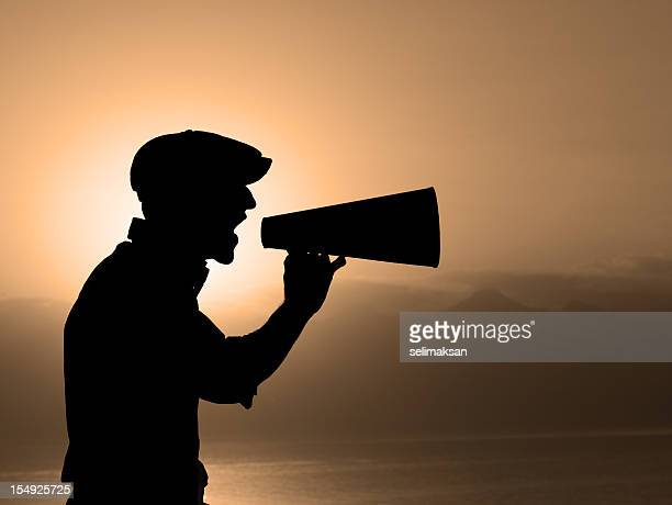 Silhouette Of Man Yelling Trough A Megaphone In Sunset