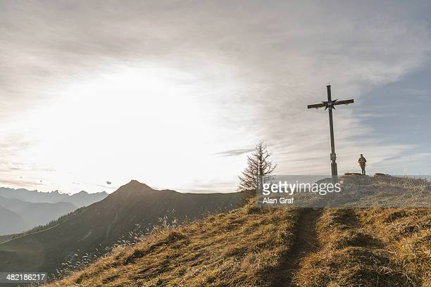 Silhouette of mid adult woman and wooden cross, Achensee, Tyrol, Austria