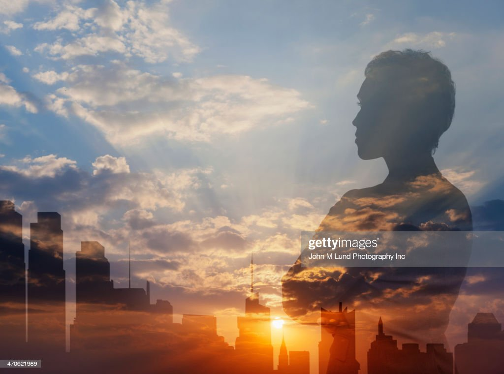 Silhouette of mixed race businesswoman and city skyline : Stock Photo