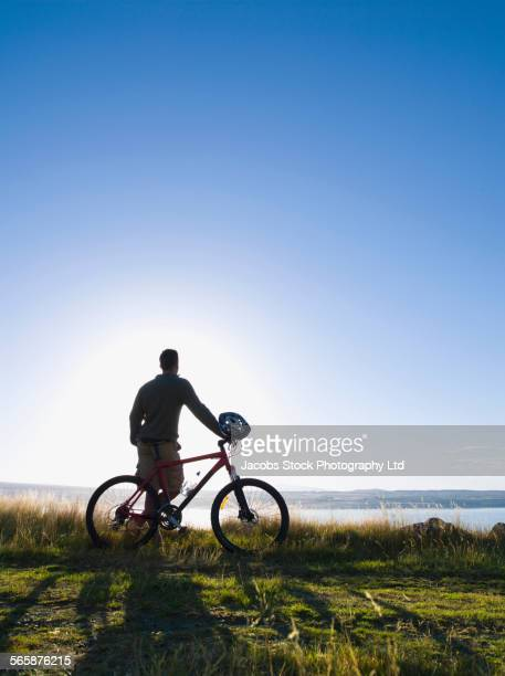 Silhouette of mixed race man holding mountain bike in remote field