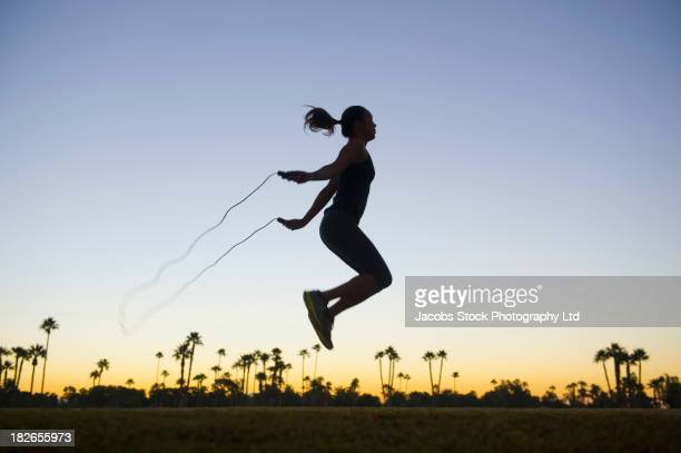 Silhouette of mixed race woman jumping rope at sunrise