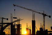 Silhouette of modern construction site with couple of tower cranes at sunset.