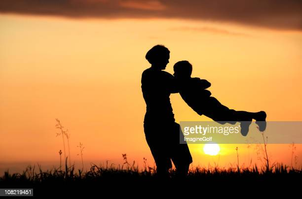 Silhouette of Mother and Child Playing at Sunset