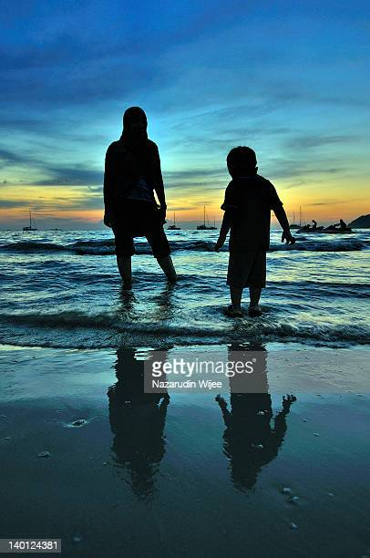 Silhouette of mother and son at beach