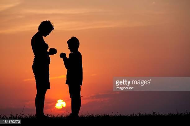 Silhueta de mãe e filho Rezar