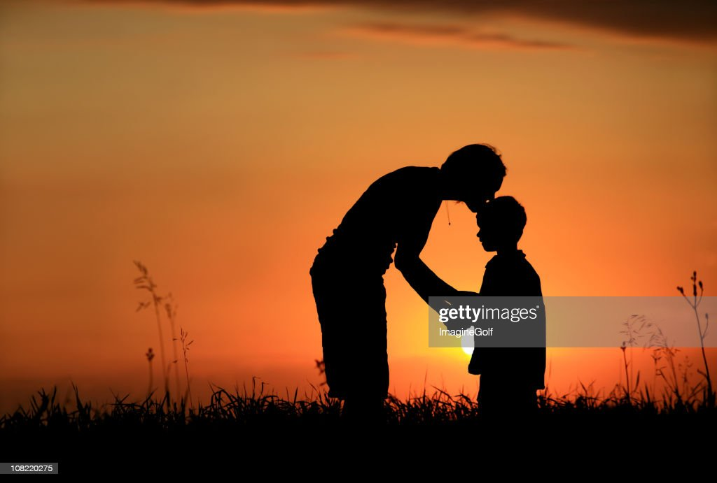 Silhouette of mother kissing child on head : Stock Photo