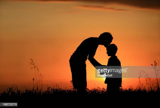 Silhouette of mother kissing child on head