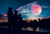 Silhouette of mother and children looking at red super moon or blood moon on colorful sky with cloud. Serenity nature background. Happy family spending time together. The moon taken with my camera.