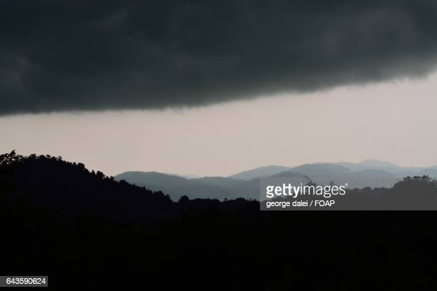 Silhouette of mountain against stormy cloud