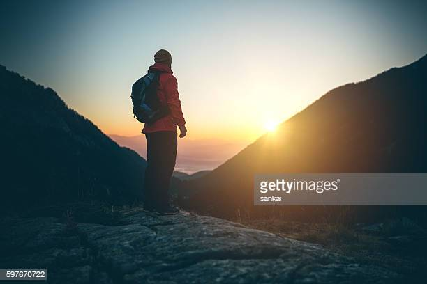 Silhouette of mountaineer on top of the mountain