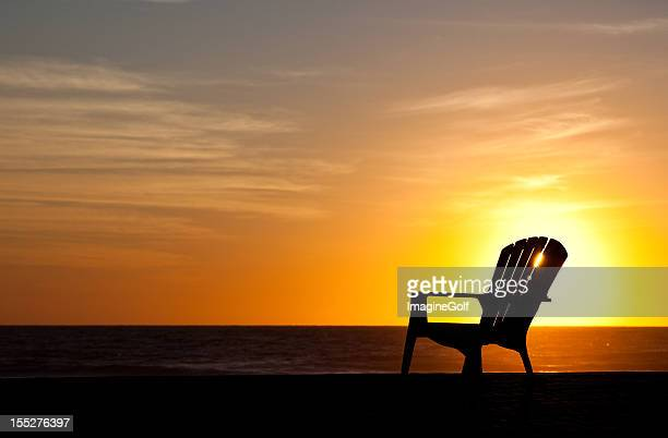 Silhouette of Muskoka Chair on the Beach by Lake