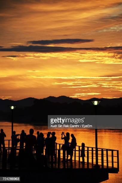 Silhouette Of People By River At Sunset