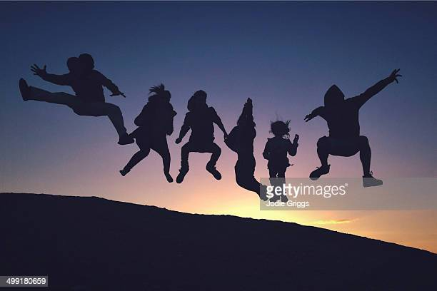 Silhouette of people jumping into air at sunset