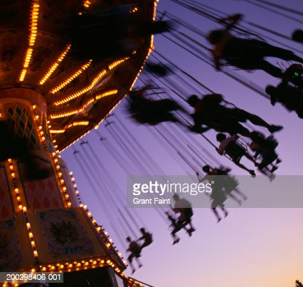 Silhouette of people on amusement park ride, dusk (blurred motion) : Stock Photo