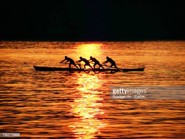 Silhouette Of People On Boat At Sunset