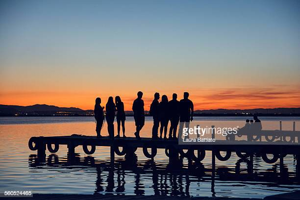 Silhouette of people on the pier at sunset