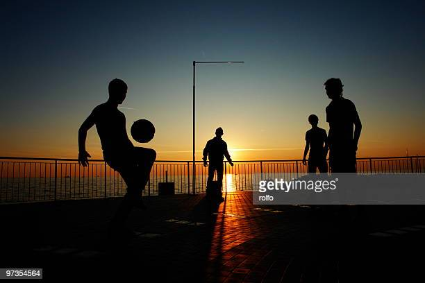 Silhouette of people playing football on beach