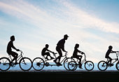 Silhouette of people riding bicycles by sea, side view