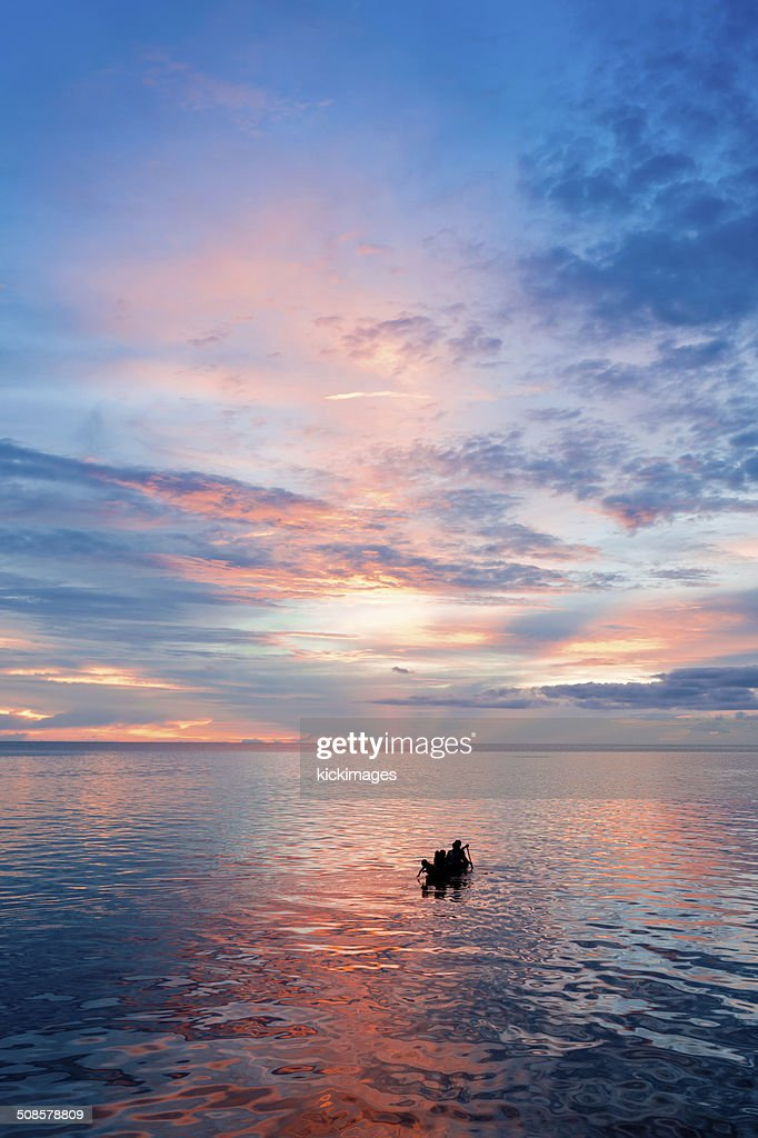 Silhouette of People Rowing Boat : Stock Photo