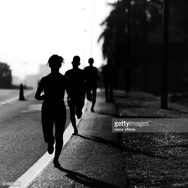 Silhouette of people running a Marathon