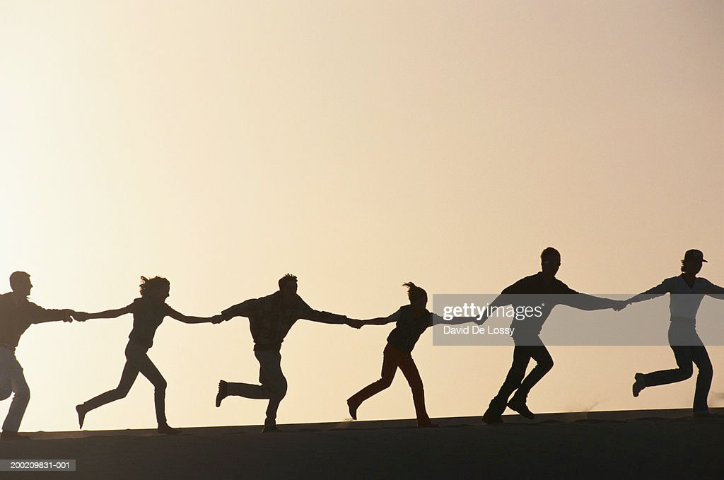 Silhouette of people running hand in hand : Stock Photo